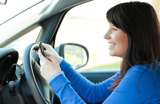 Улыбается девушка-подросток с помощью мобильного телефона во время вождения