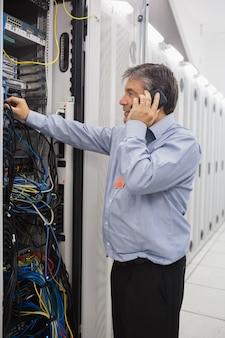 サーバの修理中に男性技術者が電話をかける