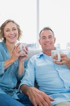 コーヒーを持つソファに座っている幸せな中年のカップル