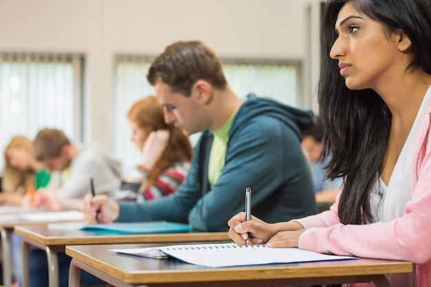 若い生徒が教室にノートを書く
