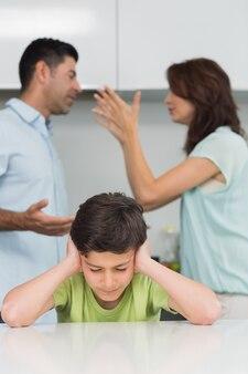 両親がキッチンで喧嘩する間、耳を覆う男の子