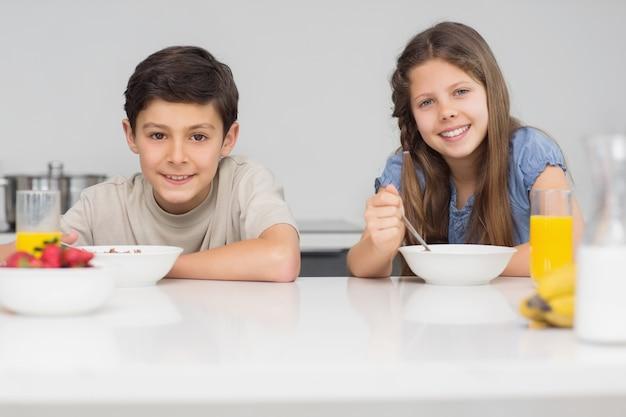 キッチンで朝食を楽しむ笑顔の若い兄弟