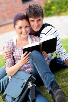 芝生に座っている本を読んでいる学生のカップルの笑顔