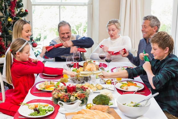 夕食のテーブルでクリスマスのクラッカーを引っ張っている家族