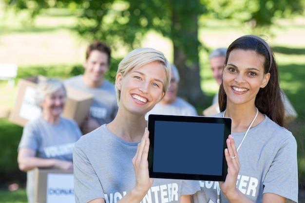 Счастливые друзья-добровольцы, показывая планшетный пк