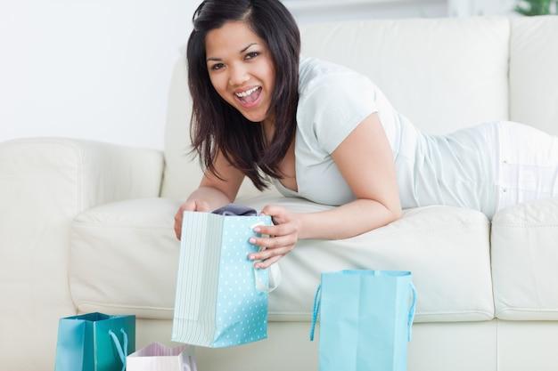Женщина, подняв сумку, лежа на диване