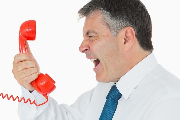 電話機で叫んでいるビジネスマン