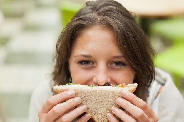 Студентка с бутербродом в столовой