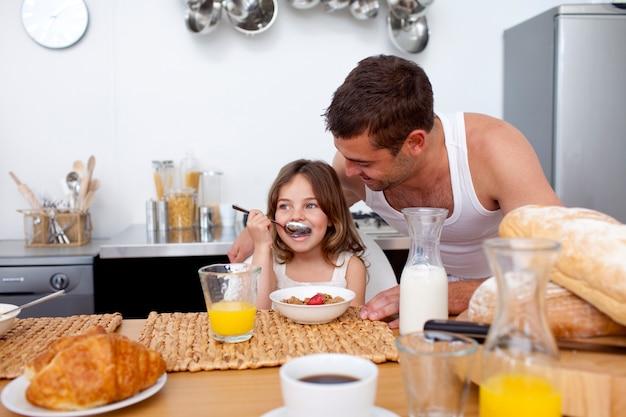 朝食の穀物や果物を食べる娘