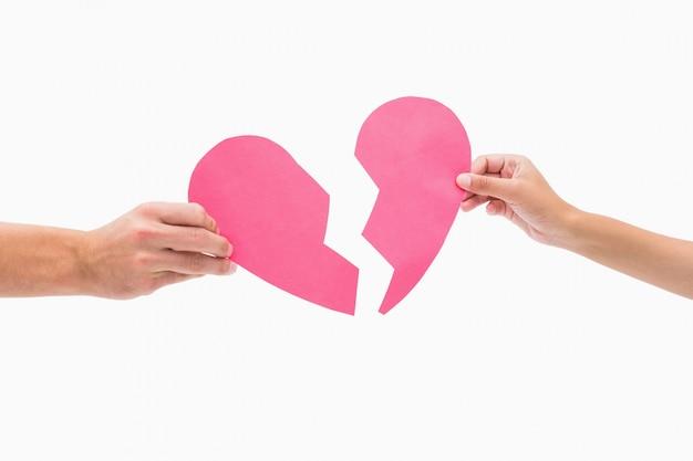 Руки с двумя половинами разбитого сердца