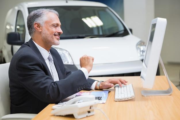 ラップトップを使って笑顔のビジネスマン