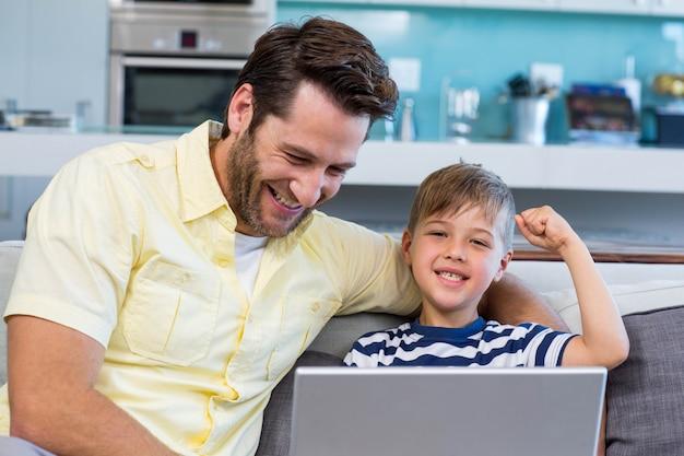 父と息子、ラップトップをソファで使用