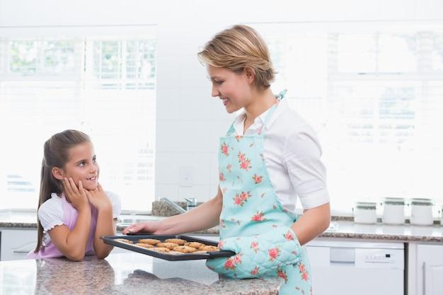 母親と娘が熱い新鮮なクッキーで