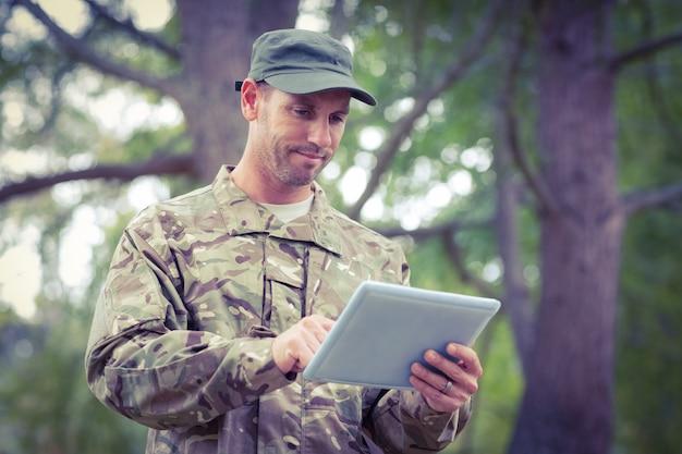 Солдат смотрит на планшетный пк в парке