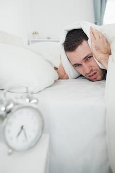 彼の目覚まし時計が鳴っている間に羽毛布団で耳を覆う男の肖像