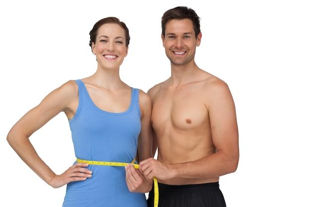 Подходящий молодой человек, измеряющий талию женщины
