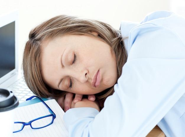 机の上で眠っている疲れた実業家