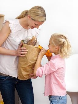 Маленькая девочка, распаковывающая продуктовый портфель с матерью
