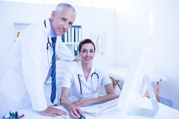 Портрет улыбающихся коллег-медиков, работающих с компьютером и глядя на камеру