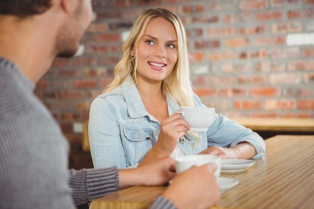 Улыбается блондинка с кофе с другом