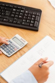 女性の手が紙の上の計算機から結果を書く