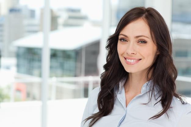 窓の前に立って立っている若い笑顔のエグゼクティブ女性