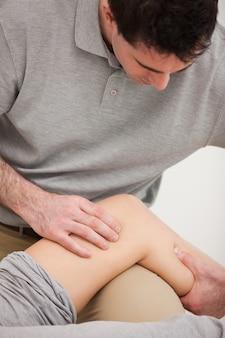 彼の患者の膝を見ている理学療法士