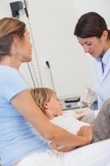 深刻な医者が子供に注射を与える