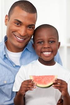 父親と果物を食べる笑顔の少年の肖像