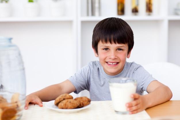 幸せな少年はビスケットを食べ、牛乳を飲む