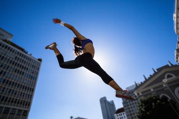 空中でジャンプするアスレチックな女性