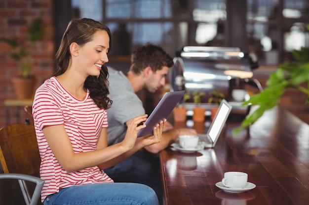 タブレットコンピュータを使用して笑顔の若い女性