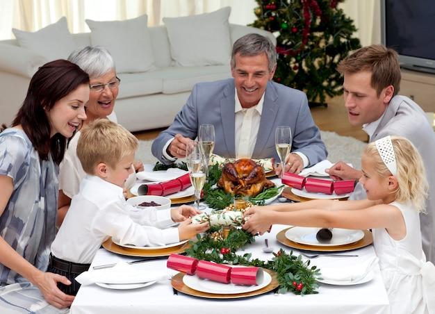 自宅でクリスマスクラッカーを引っ張っている子供たち