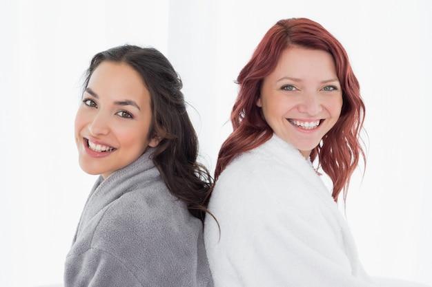 Женские друзья в халатах, стоящих спиной к спине