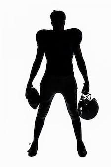 Силуэт американского футболиста, держащего мяч и шлем