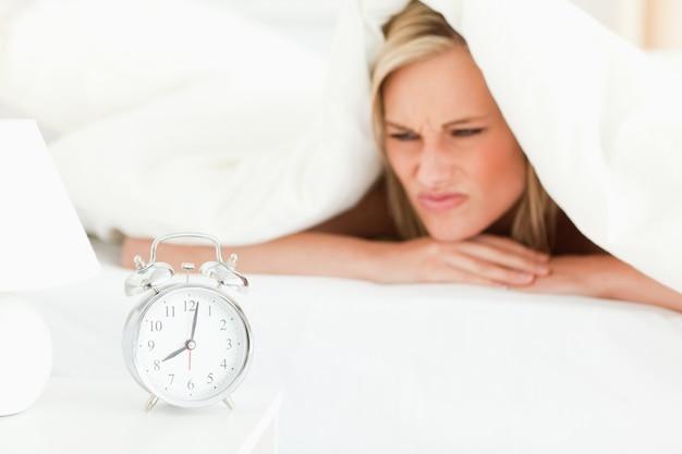不満を抱くブロンドの女性が目を覚ます