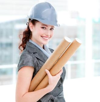 青写真を保持している笑顔の女性の建築家の肖像
