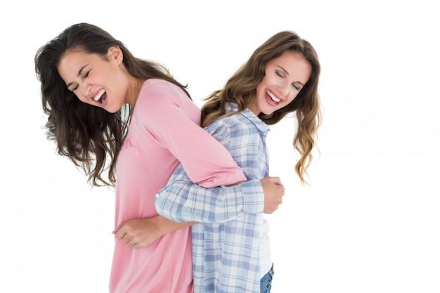 Женщины, стоящие спиной к спине со сложенными руками