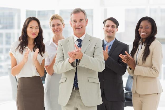 カメラで立って拍手するビジネスチーム