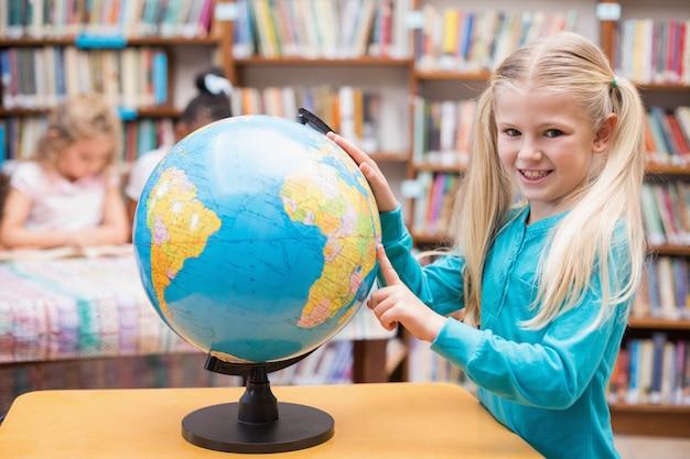 かわいい瞳孔は、図書館で地球儀を見て
