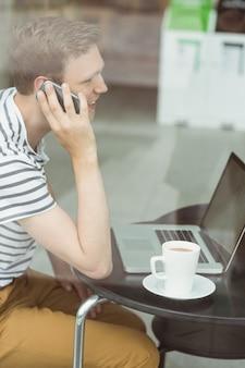 カフェでラップトップとスマートフォンを使って笑っている学生