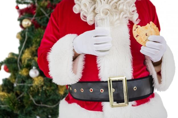 Санта держит стакан молока и едят печенье