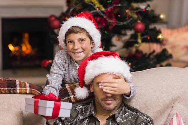 息子はクリスマスの贈り物に驚く父