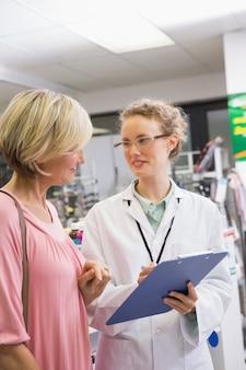 彼女の顧客と処方箋を書く薬剤師