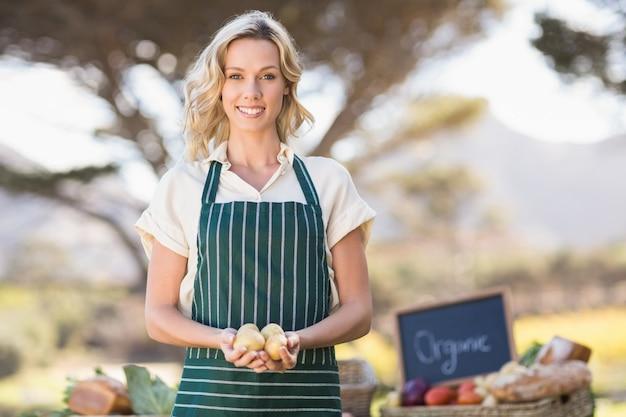 ジャガイモを持っている笑顔の農夫女性