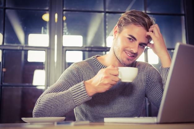 コーヒーを飲んで笑顔でハンサムな男
