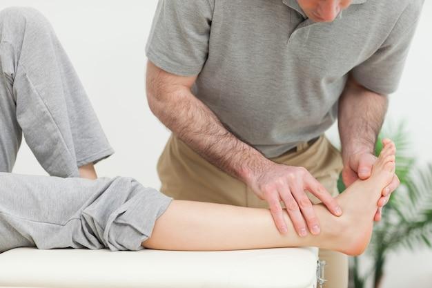 女性の足元を診察する医師