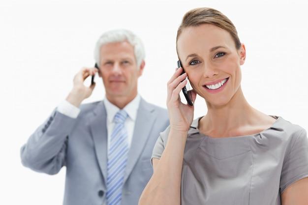 白い髪の男と電話をかける笑顔の女性のクローズアップ