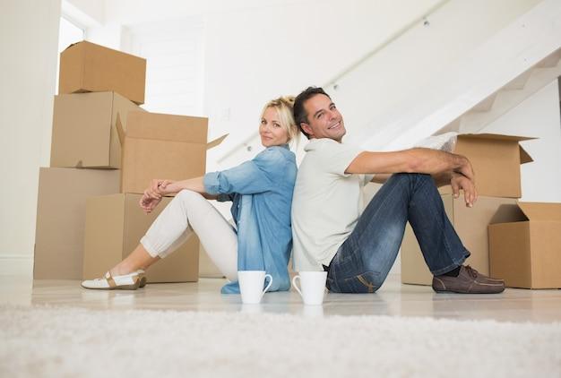 新しい家のカップとボックスで笑顔カップル