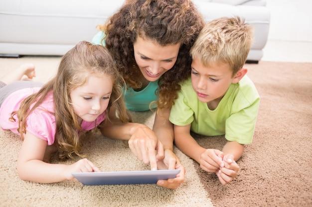 Счастливые братья и сестры, лежащие на коврике, используя планшет с матерью